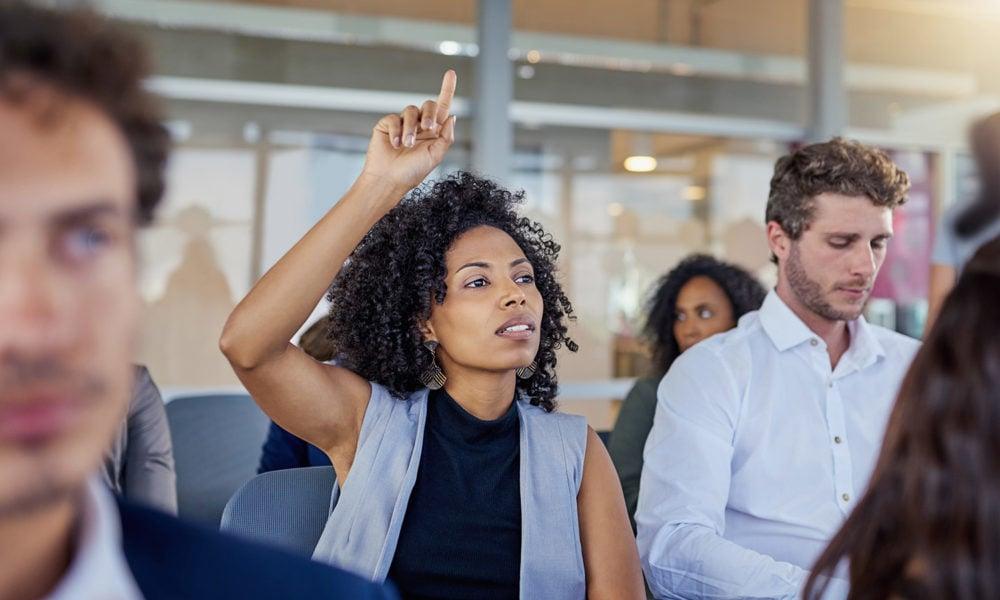 Woman raising hand at meeting