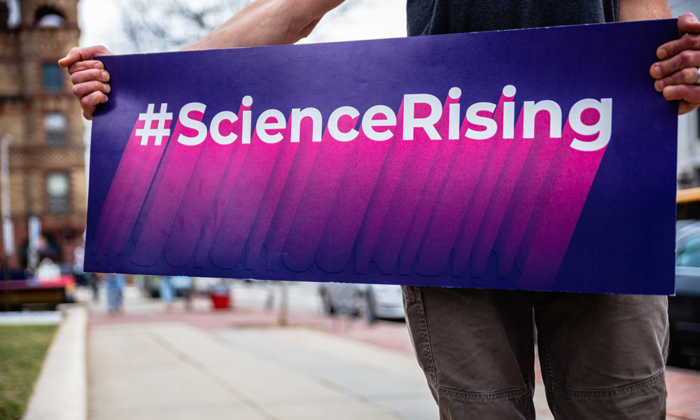 Man holding Science Rising sign on city street