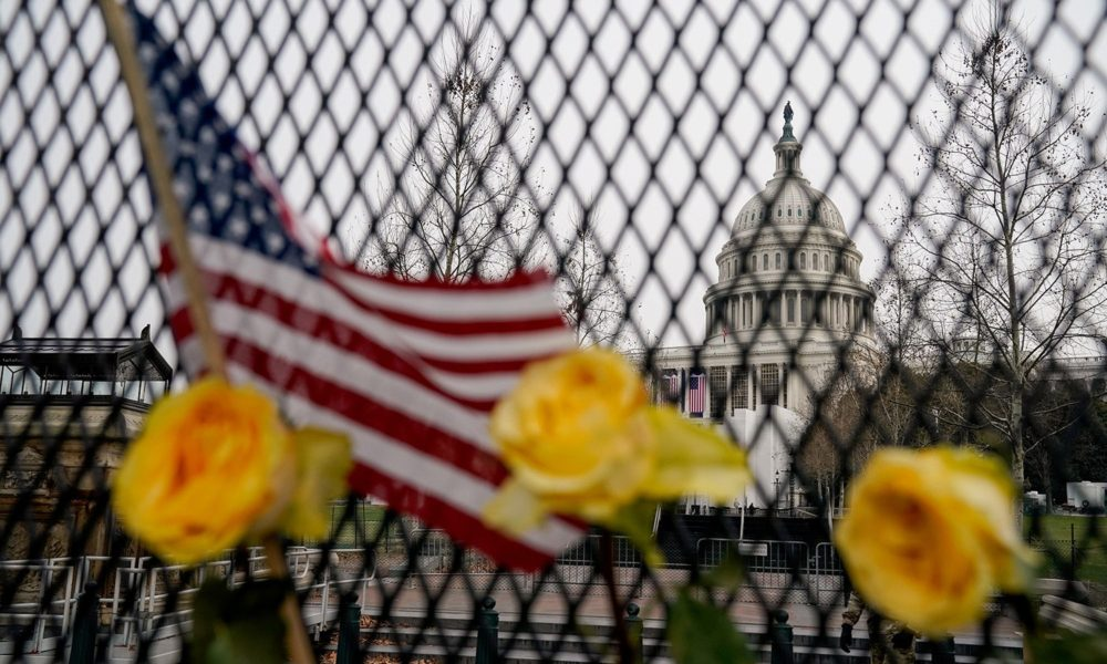 The US Capitol seen through a fence with flowers and a US flag inserted in it