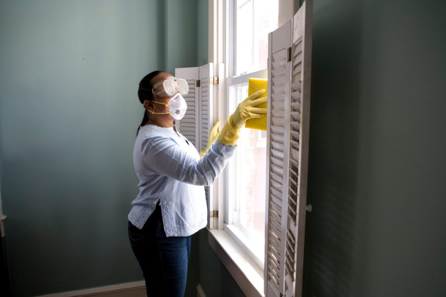 A woman cleans a window wearing protective gear including goggles and a face mask