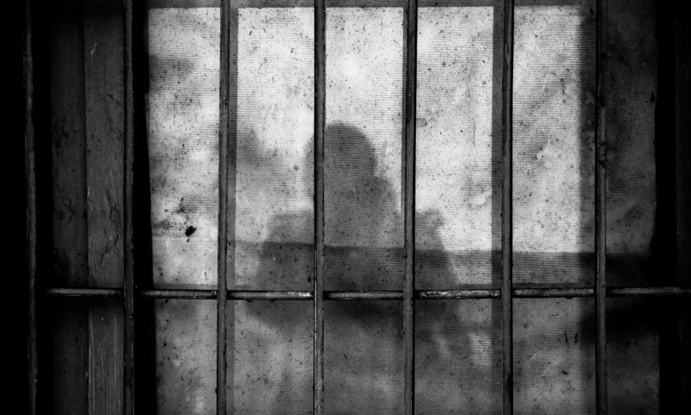 Image of prison bars with a person's shadow behind them.