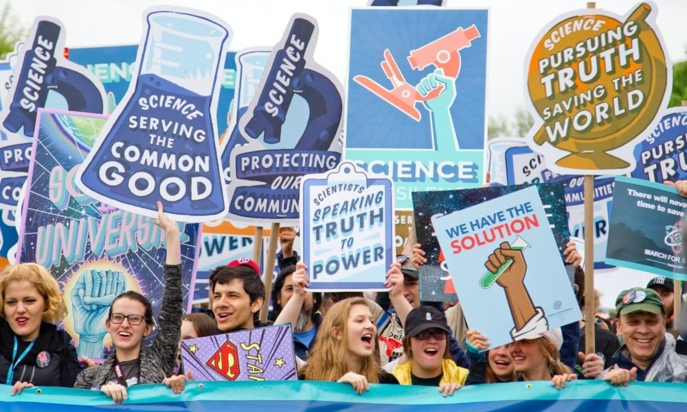 """a group of science activists marches for science, holding signs that say """"Scientists speaking truth to power,"""" and """"science serving the common good"""""""